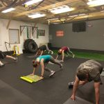boot camp fitness class performing crossbody mountain climbers in catalyst 4 fitness studio