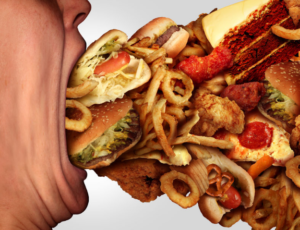 a man trying to stuff a very large amount of food in his mouth
