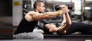 trainer helping woman with a flat bench chest flye