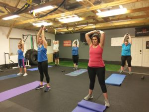 overhead dumbbell tricep extensions being performed by small group fitness class in catalyst 4 fitness studio