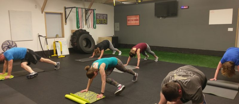 a fitness class performing crossbody mountain climbers