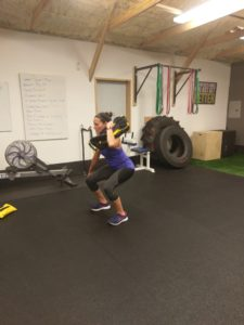 sandbag squat performed by woman in personal training session in catalyst 4 fitness studio