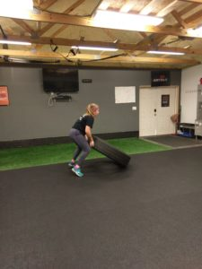 a woman flipping a tire in personal training session in catalyst 4 fitness studio