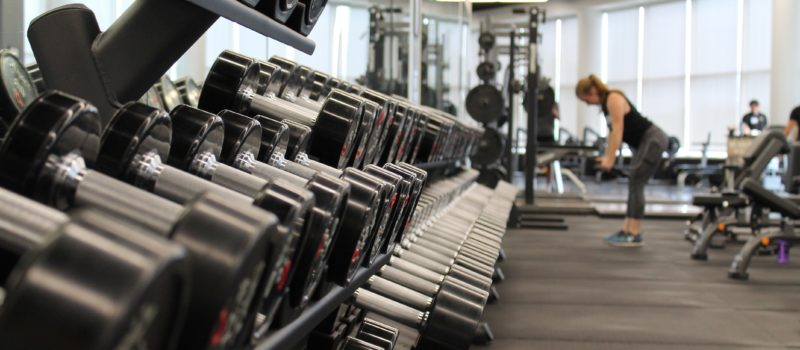 racks of dumbbells and a woman lifting weights